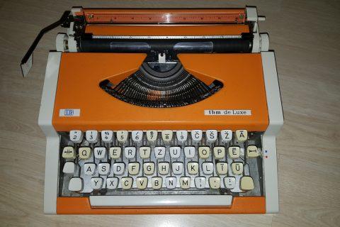Rakstīšanas ierīce, kurā tekstu veido reljefas metāla zīmes, kas ar īpašu mehānismu piespiež krāsu lenti pie papīra